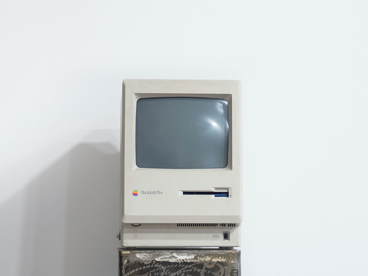 Old computer sitting alone in a white room