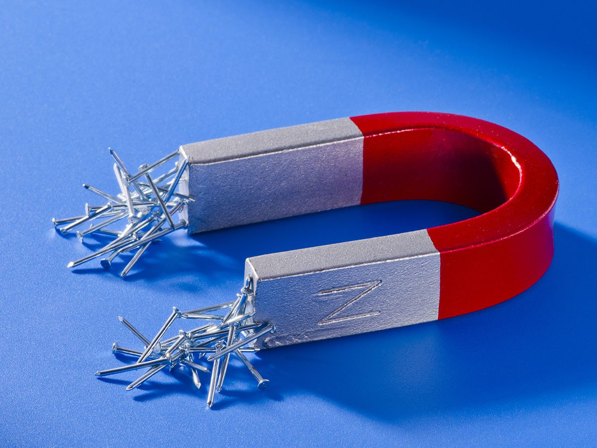 Red and chrome magnet with small nails sticking to the ends sitting on a blue surface