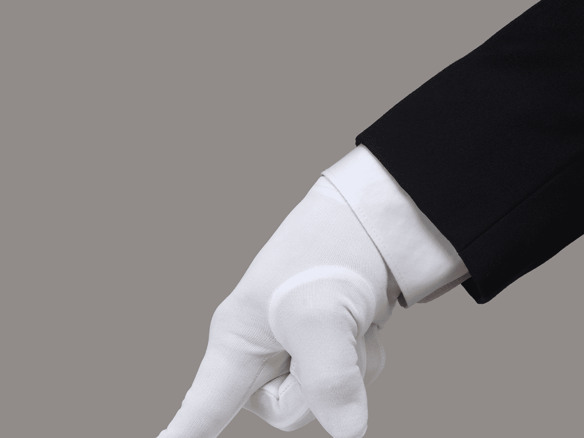 Person in a fancy suit with white gloves pressing down with their pointer finger on an unseen surface